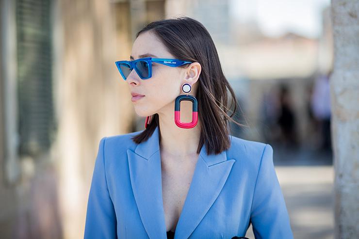 девушка вголубом пиджаке, очках икрупных серьгах