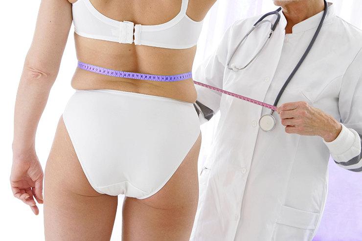 врач измеряет фигуру пациентки