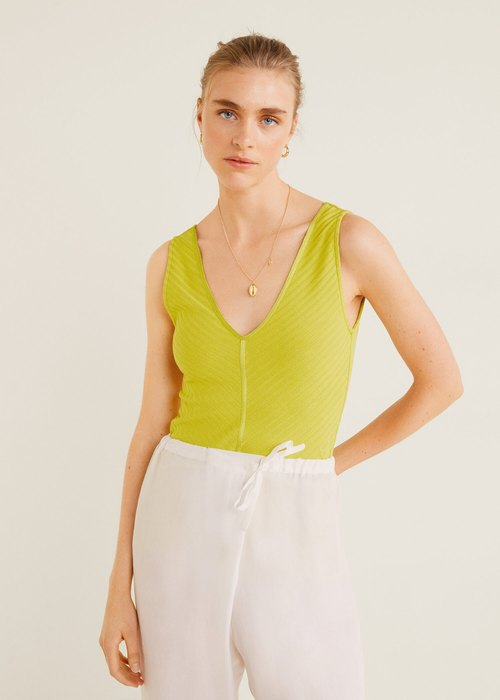 модель взеленой майке ибелых брюках