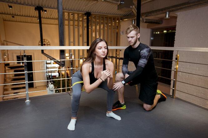 девушка тренируется в зале с фитнес-инструктором