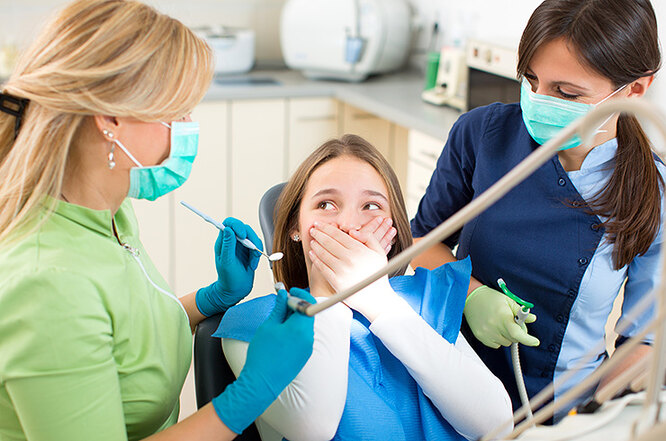два стоматолога и пациент-подросток