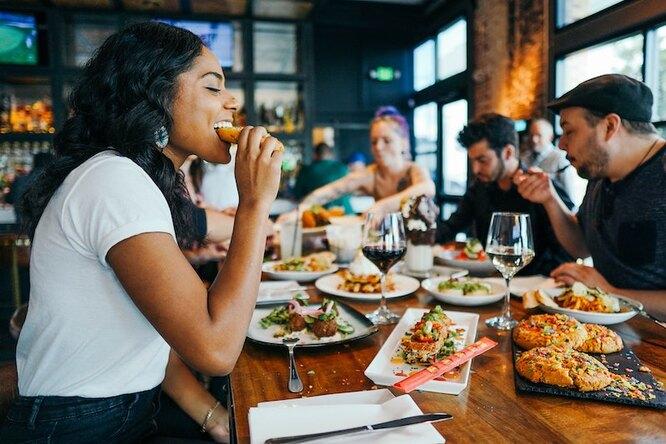 Компания в ресторане ест, девушка на переднем плане откусывает кусочек гамбургера