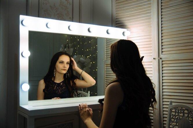 Девушка смотрит в зеркало и ищет признаки гормональных сбоев