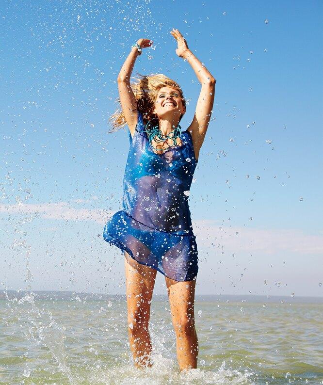 Женщина в синем руки вверх по воде ногами на море