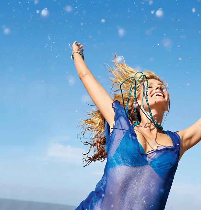 Женщина в синем на фоне неба и счастлива