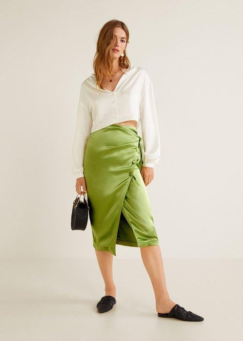 модель в белой кофте и зеленой юбке