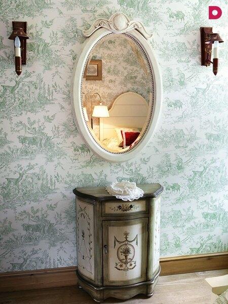 Фрагмент гостевой спальни с расписанным деревянным комодом и выбеленным зеркалом.