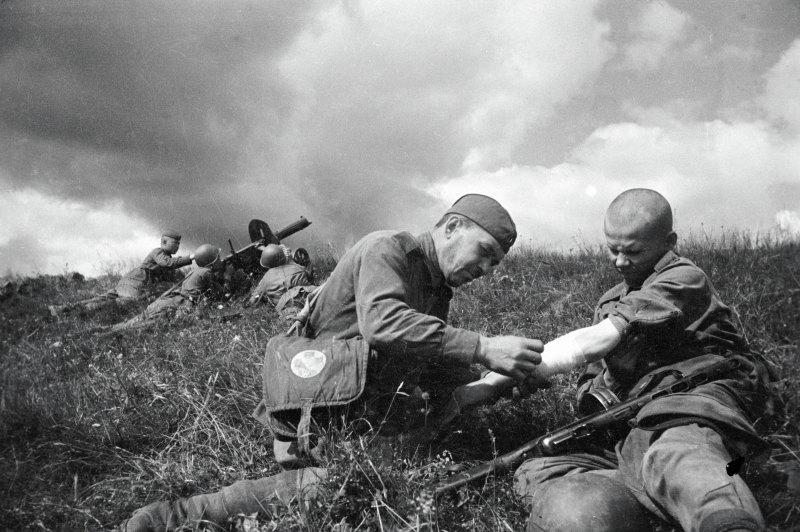Санитар перевязывает руку раненому солдату