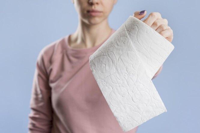 Девушка вытянула руку с туалетной бумагой, призыв не терпеть в туалет