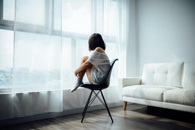Девушка на стуле с ногами смотрит в окно, признаки гормональных нарушений
