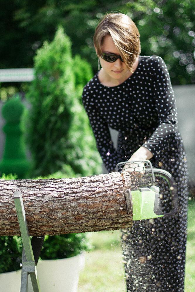 Женщина пилит дерево