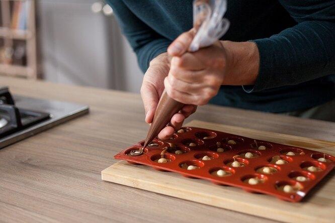Выдавливаем шоколадную пасту вокруг орехов