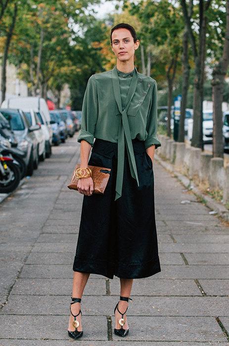 девушка в черных брюках-кюлотах и зеленой блузке