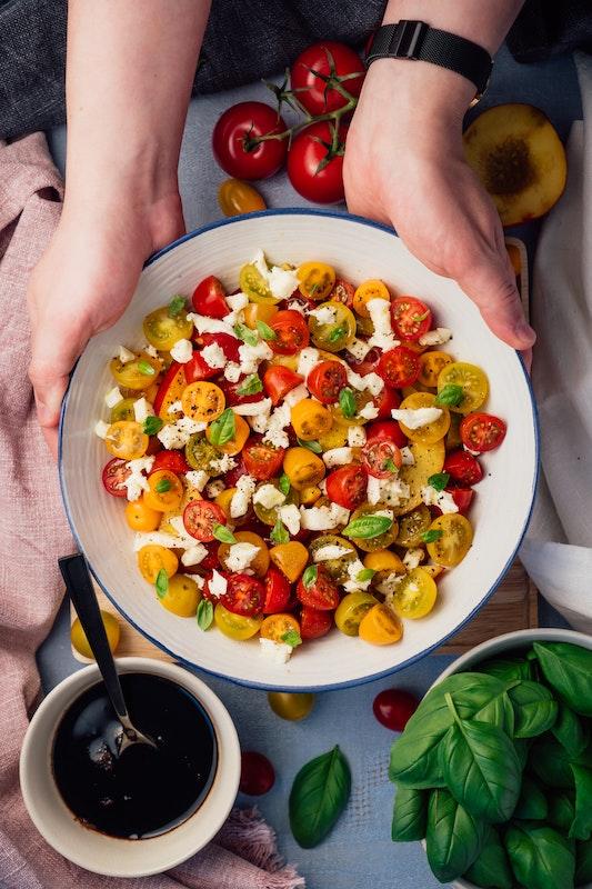 Нарезанные овощи на тарелке в руках