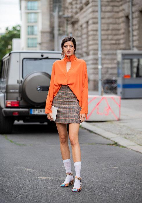 девушка в оранжевой блузке и клетчатой юбке