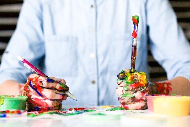 Руки, испачканные краской, рисуют и держат кисть
