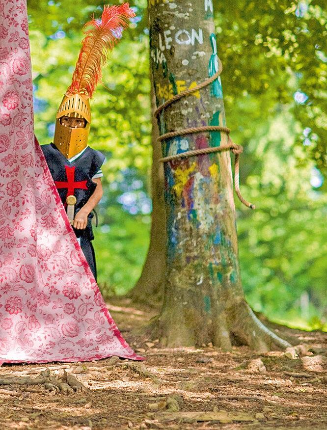 Мальчик в костюме рыцаря за деревом