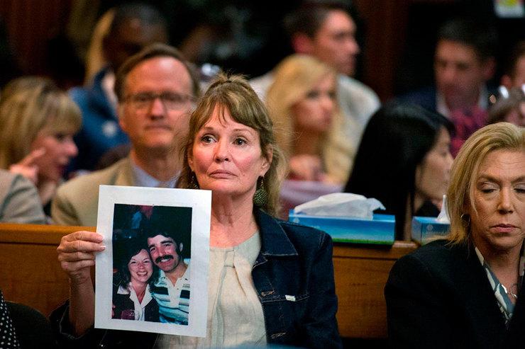 Мелани Барбо держит фотографию жертв Чери Доминго иГрега Санчеса во время предъявления обвинения Джозефу Джеймсу Де Анджело