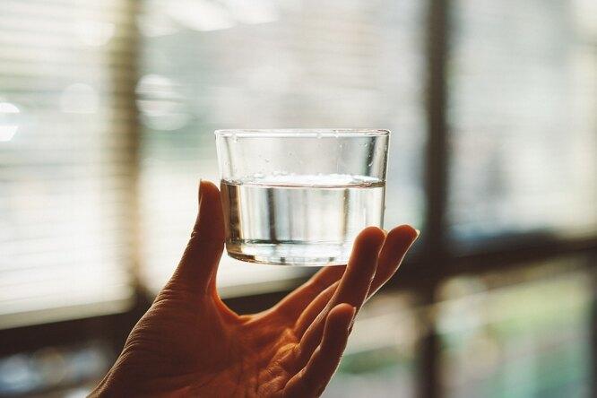 Рука держит стакан с водой, сколько нужно пить воды в сутки