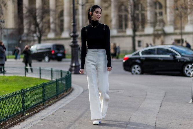 Девушка в водолазке и широких белых брюках