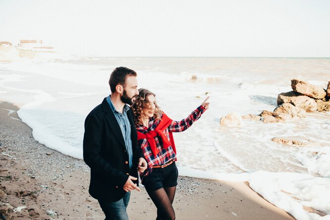 Мужчина и женщина гуляют по пляжу