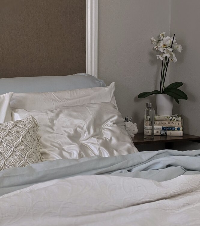 Белые шелковые подушки на кровати
