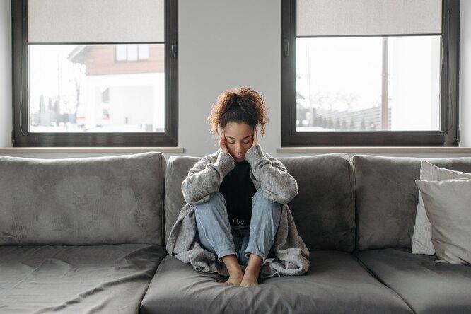 Женщина испытывает приступ головокружения, женщина сидит на диване