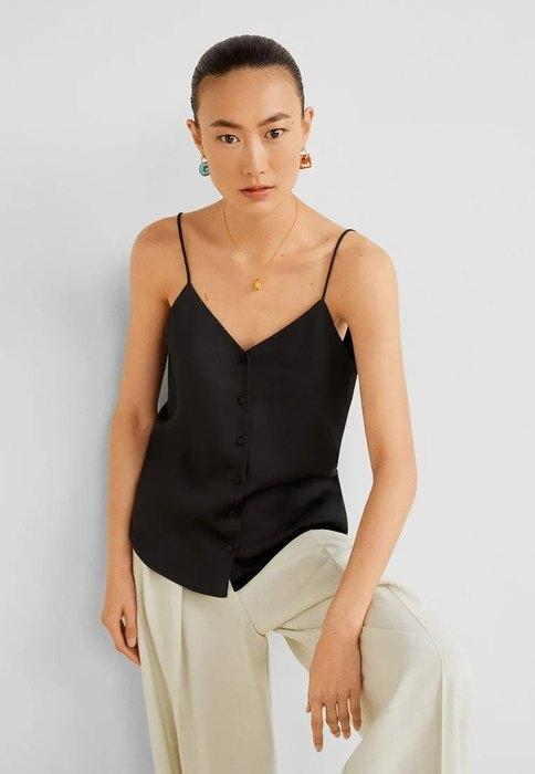 модель в черном топе и светлых брюках