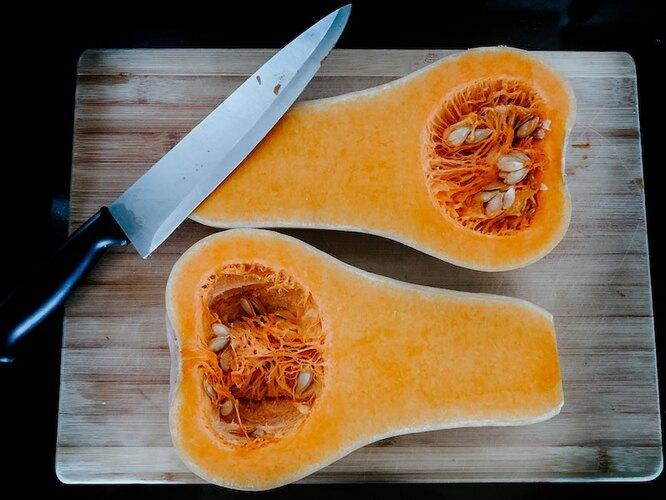 Разрезанная пополам тыква Баттернат Сквош и нож