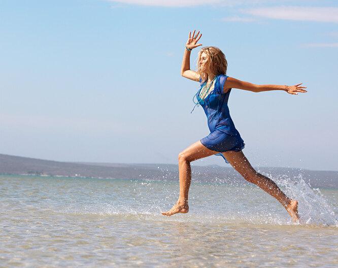 Женщина в синем бежит по морской воде
