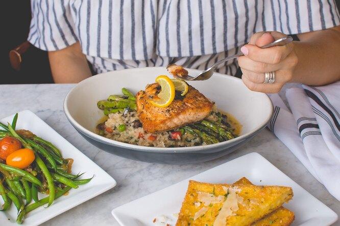 Полезно питаться, чтобы начать худеть, рука ест рыбу с овощами