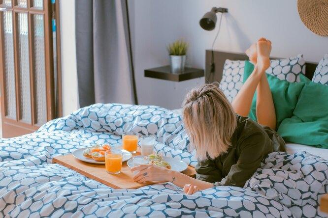 Девушка на кровати с подносом с соками и завтраком, сколько воды и другой жидкости выпивать в день
