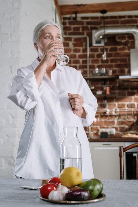 Женщина в белой рубашке пьет воду