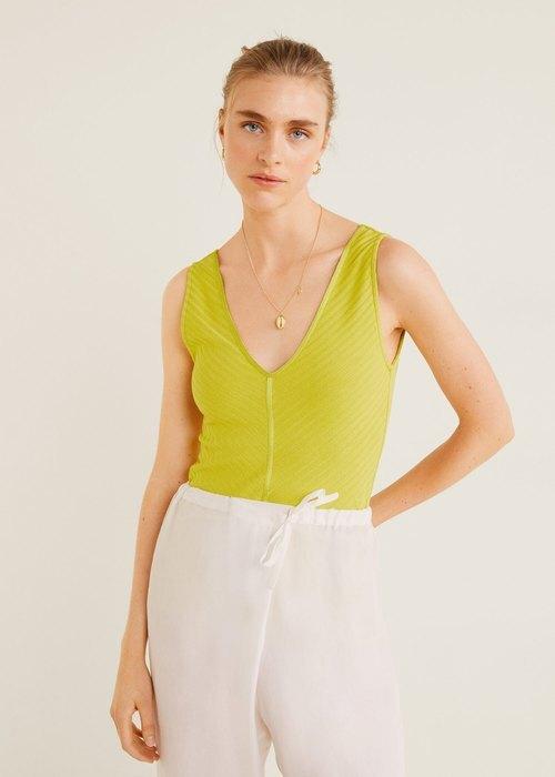 модель в зеленой майке и белых брюках