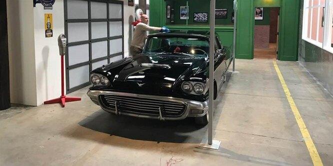 Старый автомобиль в декорациях «города»